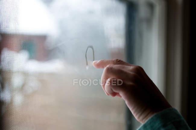 Menina desenho em condensação na janela — Fotografia de Stock