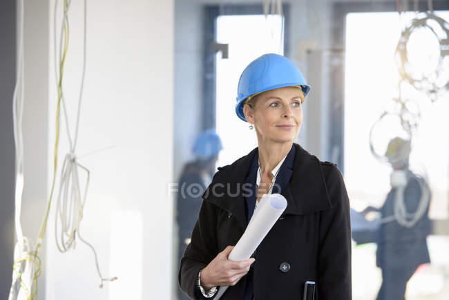 Portrait of businesswoman holding blueprint in new office — Stock Photo