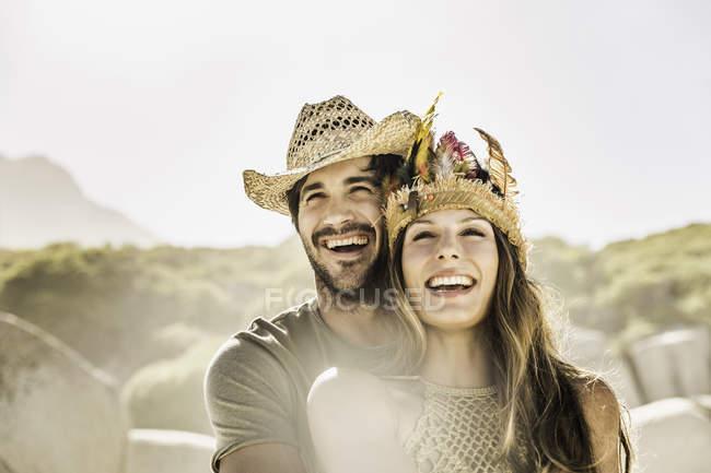 Середині дорослих пара носіння солом'яному капелюсі і головний убір на пляжі, Кейптаун, Південно-Африканська Республіка — стокове фото