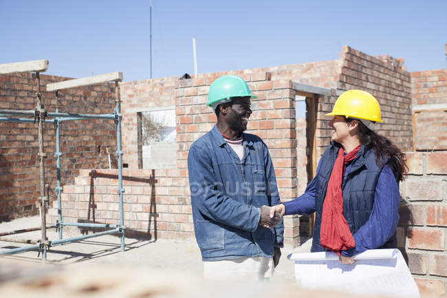 Woman and builder shaking hands on construction site — Stock Photo