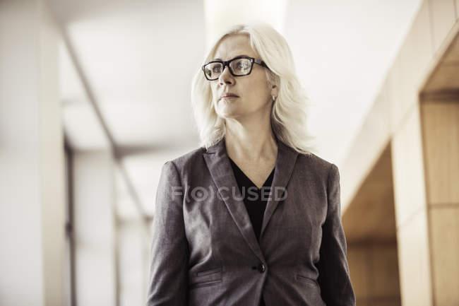 Портрет предпринимательницы, идущей по офисному коридору — стоковое фото