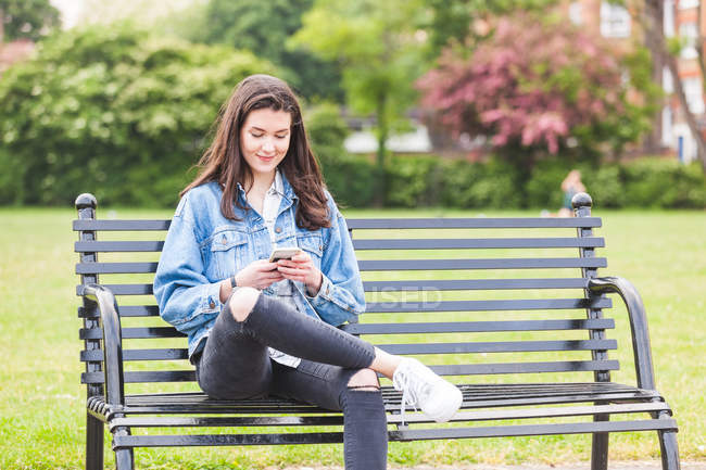 Young woman reading smartphone texts on park bench — Stock Photo