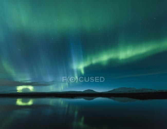 Aurora borealis reflecting in lake water — Stock Photo
