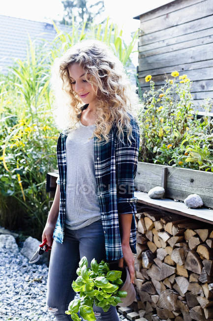 Young woman with curly blonde hair in garden, portrait — Stock Photo