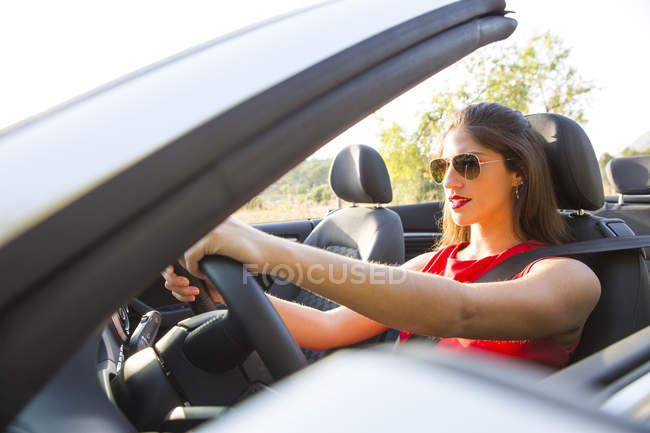 Young woman driving on rural road in convertible, Majorca, Spain — Stock Photo