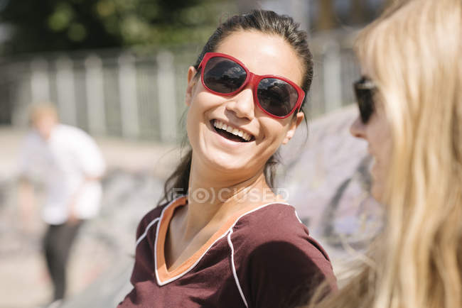Two female skateboarding friends laughing in skatepark — Stock Photo
