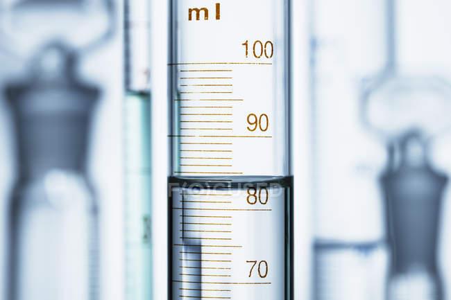 Меніск води в дозованого циліндр, обсягу рідини вимірюється, читаючи масштабу в нижній частині меніск — стокове фото