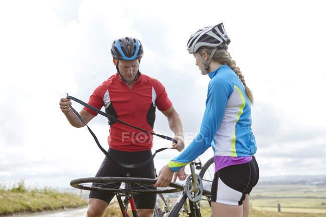 Cyclists fixing wheel on roadside — Stock Photo