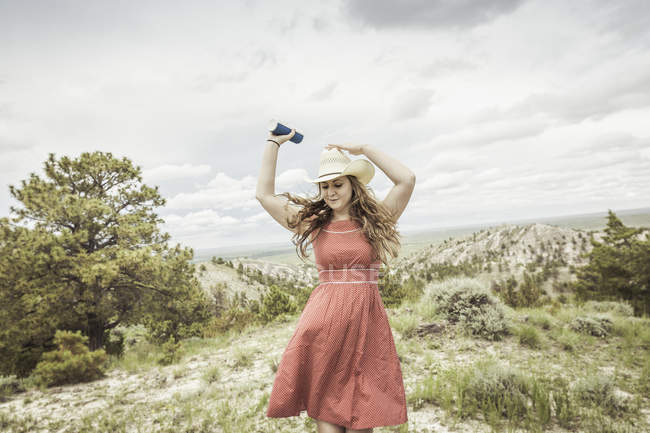 Young woman wearing red dress and stetson dancing on hilltop, Cody, Wyoming, USA — Stock Photo