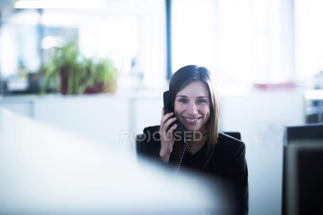 Jovem no escritório usando telefone olhando para a câmera sorrindo — Fotografia de Stock