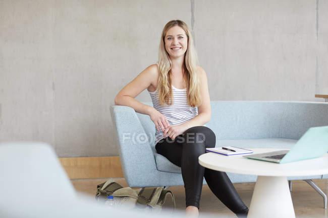 Портрет молодой студентки, сидящей на диване в высшем учебном заведении — стоковое фото