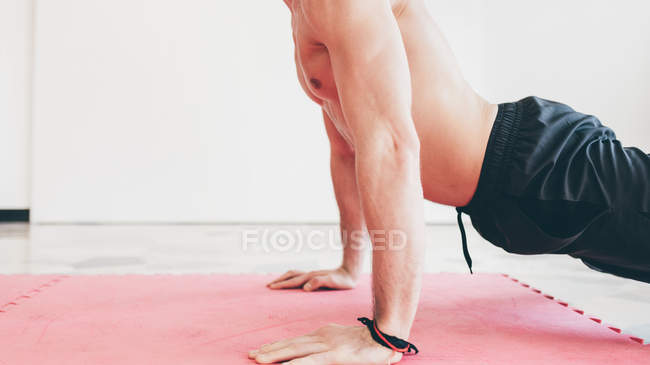 Side view of man in gym doing push ups — Stock Photo