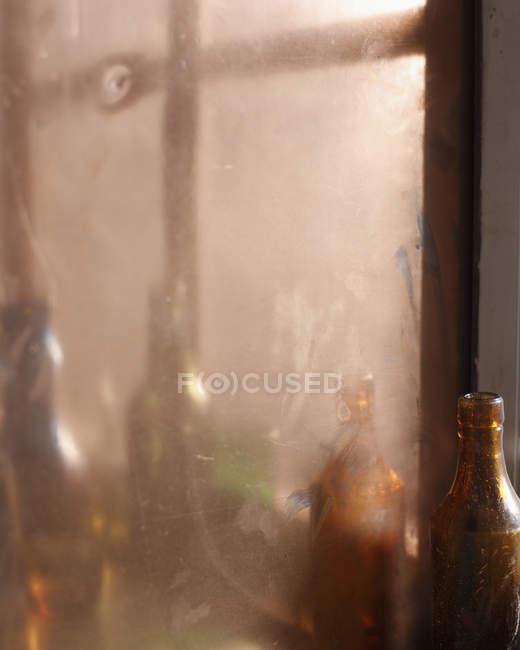 Riflessione di bottiglie di vino vuote nello specchio — Foto stock
