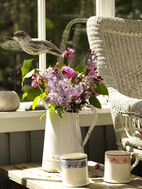 Arreglo floral en jarra rústica en la mesa auxiliar del conservatorio - foto de stock