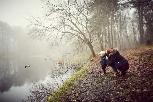 Взрослая женщина, приседающая с малышом-сыном на туманном берегу реки — стоковое фото