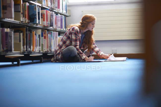 Jeune étudiante du collège écrivant des notes sur le sol de la bibliothèque — Photo de stock