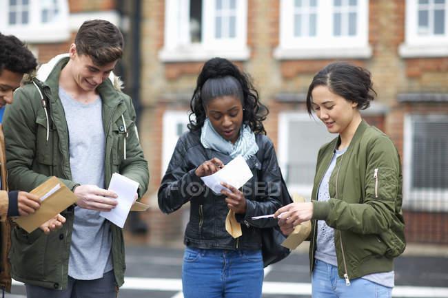 Jeunes adultes étudiants lecture des résultats de l'examen sur le campus — Photo de stock