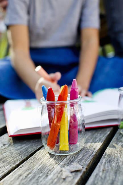 Баночка карандашами заделывают с девушкой в фоновом режиме — стоковое фото