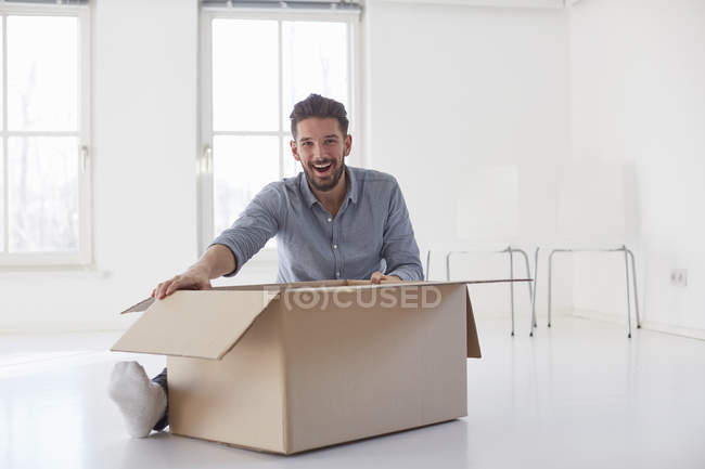 Portrait of young man sitting on floor opening cardboard box in new house — стокове фото
