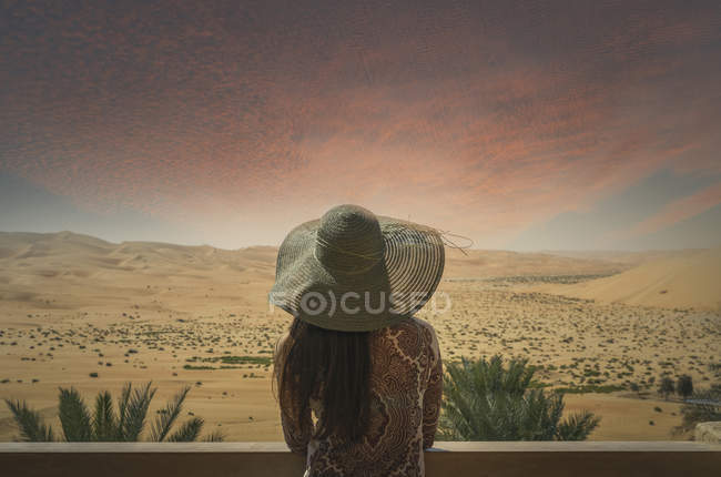 Woman on balcony, looking at desert view, at sunset, rear view, Abu Dhabi — Stock Photo