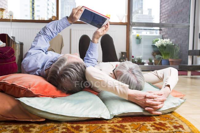 Pareja usando tableta digital en el suelo - foto de stock