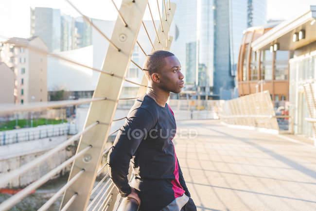 Молодой человек стоит на пешеходном мосту, задумчивое выражение лица — стоковое фото
