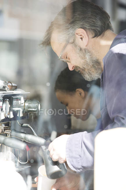 Window view of owner and waitress making fresh coffee in cafe — Stock Photo