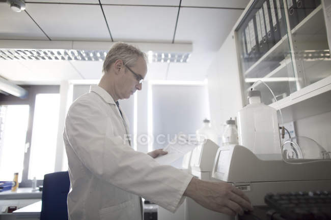 Male meteorologist reading data from weather station laboratory — Stock Photo