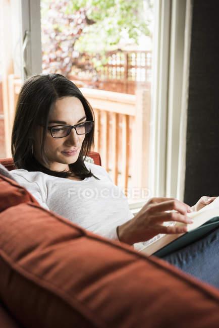 Женщина читает книгу на диване дома — стоковое фото