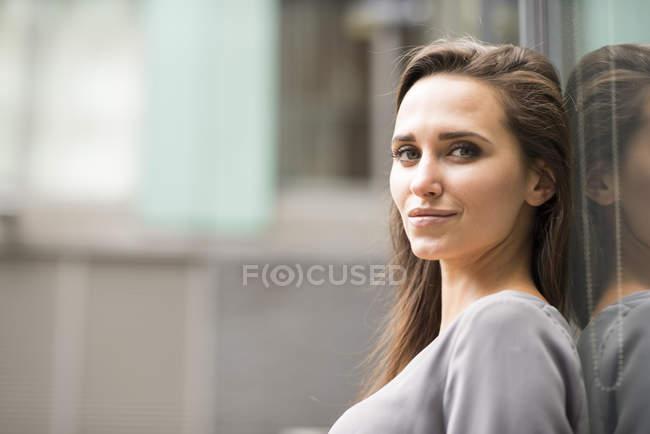 Ritratto di giovane imprenditrice appoggiata all'esterno dell'ufficio, Londra, Regno Unito — Foto stock