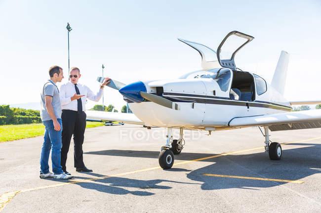 Piloto de hablar con el pasajero del avión antes de despegue - foto de stock