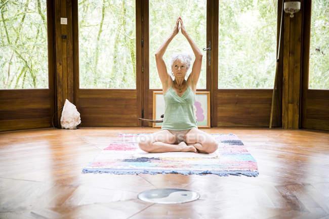 Femme en position d'yoga assis sur le plancher en bois — Photo de stock