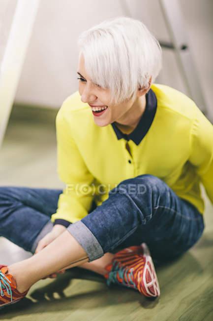 Студія постріл жінка з платини Блонд волосся сидить на підлозі — стокове фото