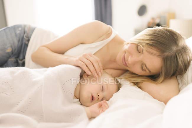 Madre guardando oltre dormire bambino su letto a casa — Foto stock