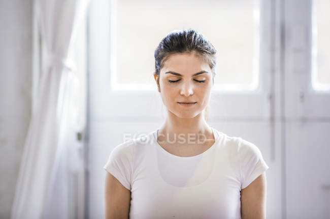 Young woman meditating with eyes closed in apartment — Stock Photo