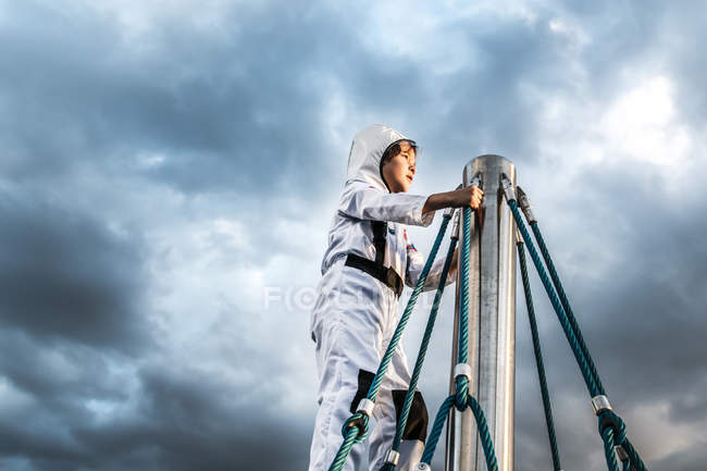 Boy in astronaut costume gazing from top of climbing frame against dramatic sky — Stock Photo