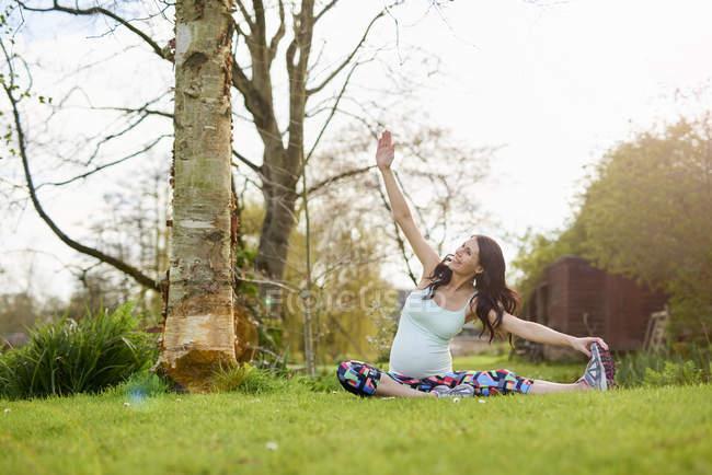 Беременная женщина тренируется на открытом воздухе, растягивается — стоковое фото