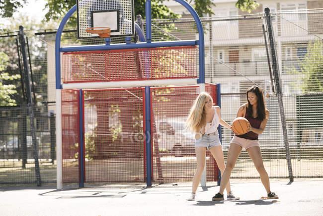 Две женщины, практикующие на баскетбольную площадку — стоковое фото