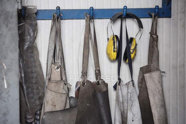 Карпентер Фартухи висить в ряд на гачки — стокове фото