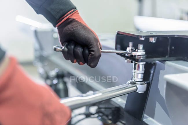 Gloved hands using spanner and ratchet on automotive production line — Stock Photo