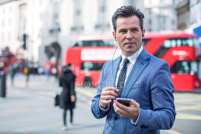 Empresários na rua com smartphone e fones de ouvido, Londres, Reino Unido — Fotografia de Stock