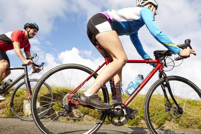 Vue latérale des cyclistes circulant sur la route de campagne par temps ensoleillé — Photo de stock