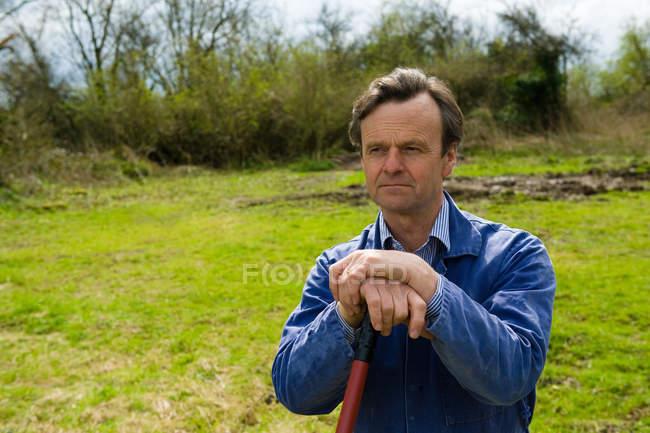 Bauer lehnt auf Mistgabel im Feld — Stockfoto