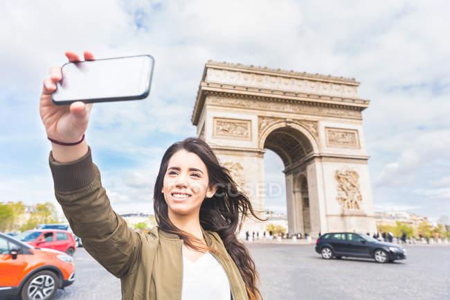 Молода жінка, беручи selfie смартфон з фонтаном, Париж, Франція — стокове фото