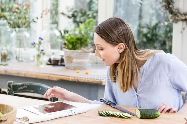 Жінка нарізки огірок, використовуючи цифровий планшетний — стокове фото