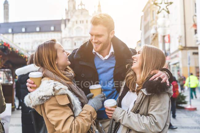 Giovane uomo e le amiche che hanno caffè da asporto al mercato di Natale — Foto stock