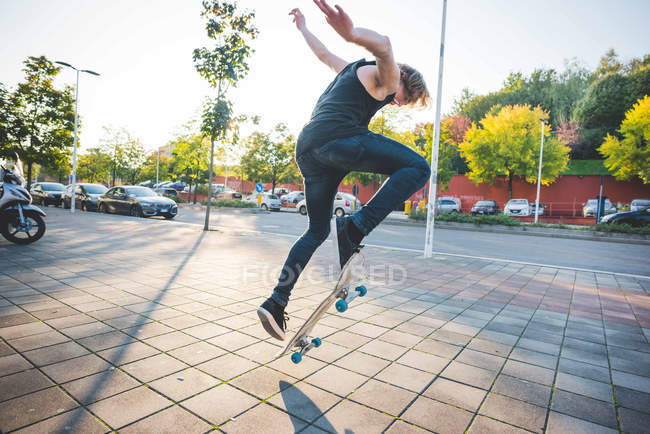 Jeune skateur urbain mâle faire truc de saut skateboard sur trottoir — Photo de stock