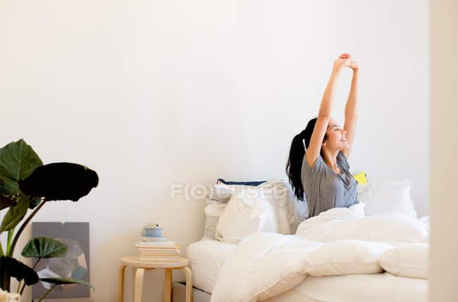Junge Frau streckte die Arme im Bett sitzend — Stockfoto