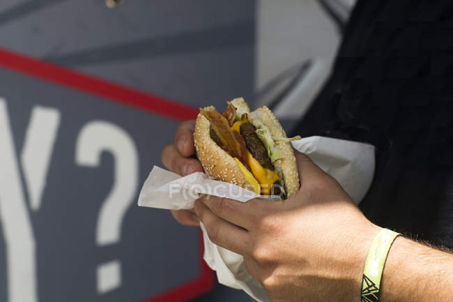 Male customer's hand eating hamburger from fast food van — Stock Photo
