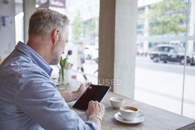 Uomo maturo seduto in un caffè, utilizzando tablet digitale, vista posteriore — Foto stock